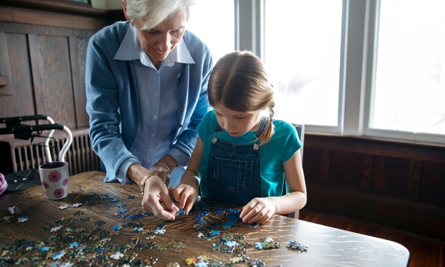 Grandmother and granddaughter assembling jigsaw puzzle